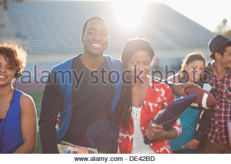 Students hugging on football field - Stock Photo