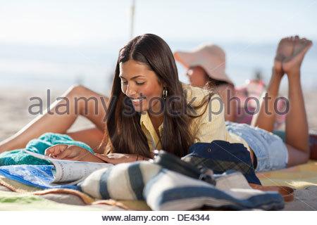 Woman sunbathing on beach - Stock Photo