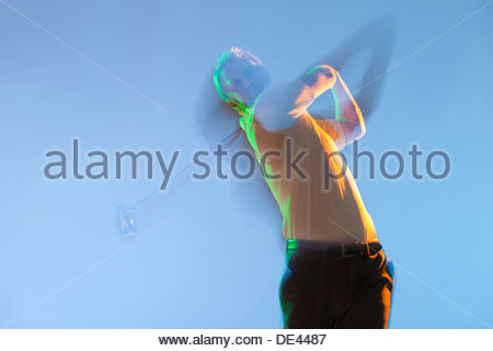 Blurred view of golf player swinging club - Stock Photo