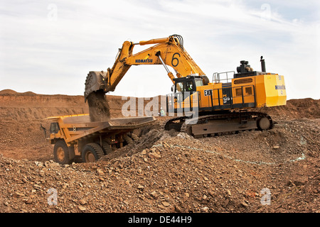 Gold mining in open cast surface pit with excavator and haul truck working, Mauritania, NW Africa - Stock Photo
