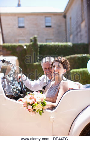 Mature bride and groom riding in convertible - Stock Photo