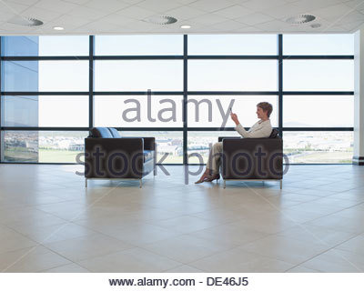 Businesswoman waiting in office waiting area and using cell phone - Stock Photo