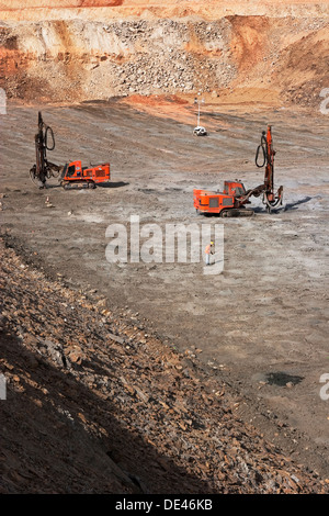 Surface gold mining, drilling holes for charges before blast  with drill machines in pit, Mauritania, NW Africa - Stock Photo