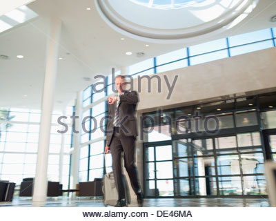 Businessman with luggage checking wristwatch - Stock Photo