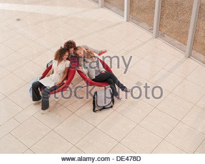 College friends view cell phone in lobby - Stock Photo