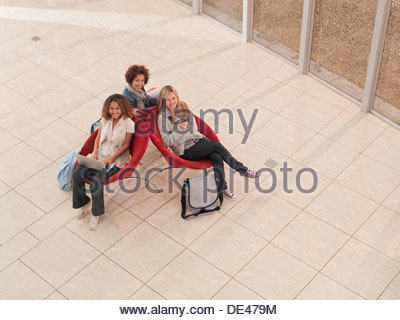 College friends using laptop and cell phone in lobby - Stock Photo