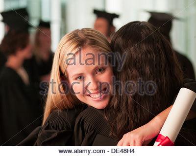 Graduates hugging - Stock Photo