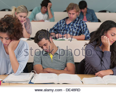Bored college students sleeping in lecture hall - Stock Photo