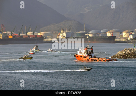 Busy harbour activity at Fujairah bunkering port  Gulf of Oman with oil tanker and storage tanks beyond (note US - Stock Photo
