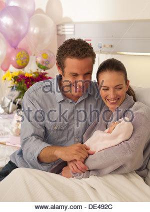 Couple holding newborn baby in hospital - Stock Photo