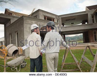 Architects  holding   blueprints outside house under construction - Stock Photo