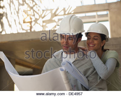 Smiling couple looking at blueprints - Stock Photo