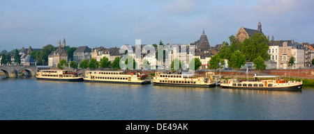Early morning view of moored sightseeing tour boats on the River Meuse Maastricht Limburg Netherlands Europe - Stock Photo