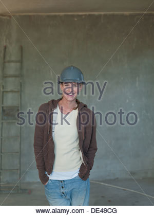 Woman in hard-hat in house under construction - Stock Photo