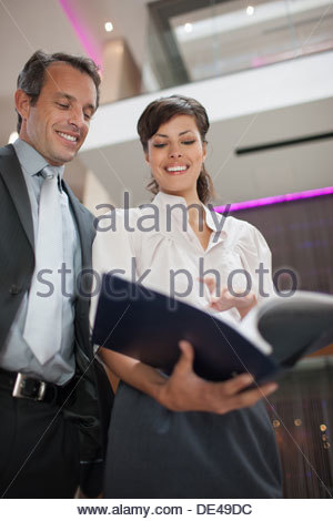 Business people reading report in lobby - Stock Photo