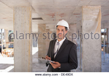 Businessman in hard-hat on construction site - Stock Photo