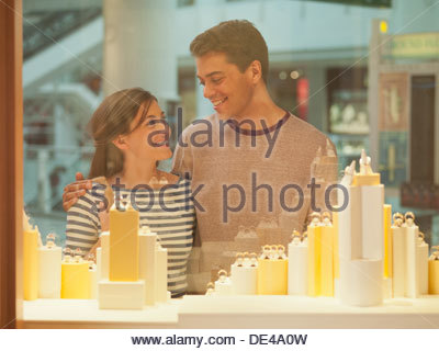 Smiling couple looking at jewelry in display case - Stock Photo