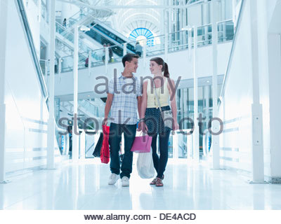 Smiling couple carrying shopping bags in mall - Stock Photo