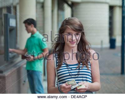 Happy girl holding money near ATM machine - Stock Photo