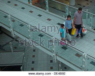 Family carrying shopping bags in mall - Stock Photo