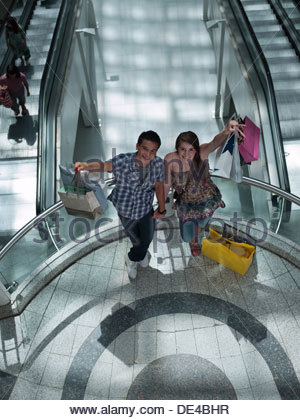 Couple holding shopping bags on balcony in mall - Stock Photo