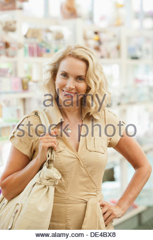 Smiling woman shopping in store - Stock Photo