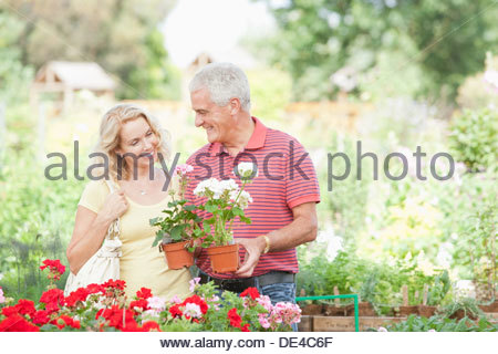 Couple shopping for flowers in nursery - Stock Photo