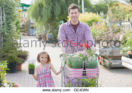 Father and daughter shopping together in nursery - Stock Photo