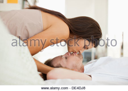 Woman kissing husband who is laying in bed - Stock Photo