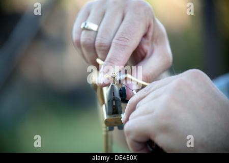 close up view of fisherman tying a fly for fly fishing using pliers and snips - Stock Photo