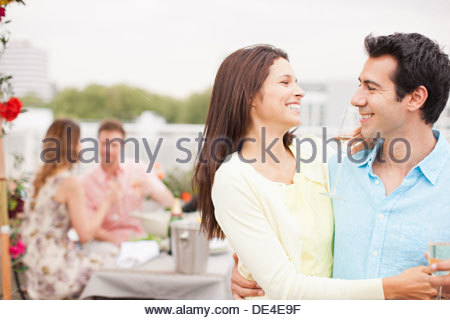 Smiling couple drinking Champagne at outdoor party - Stock Photo