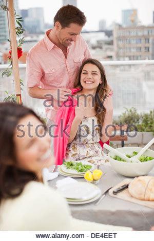 Couples enjoying party on balcony - Stock Photo