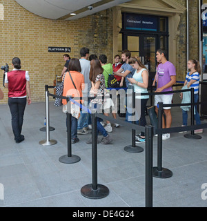 Fans queuing to have a photo taken at the platform nine and three quarters sign from Harry Potter story at Kings - Stock Photo