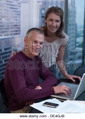 Couple working on computer with cityscape in background - Stock Photo