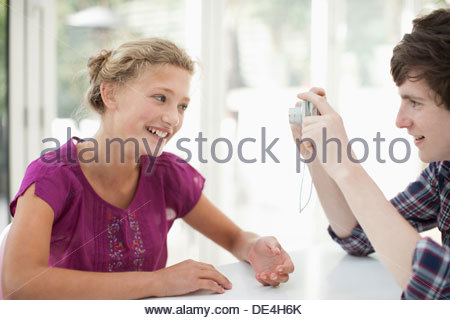 Brothers and sister taking photograph with digital camera - Stock Photo