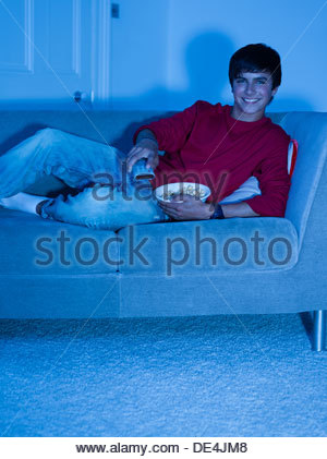 Smiling teenage boy laying on sofa with remote control - Stock Photo