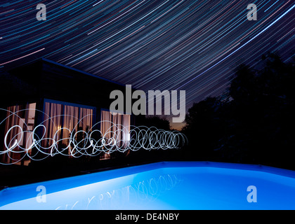 Starlight trails and floodlit swimming pool outside villa in late summer evening, southern France. - Stock Photo