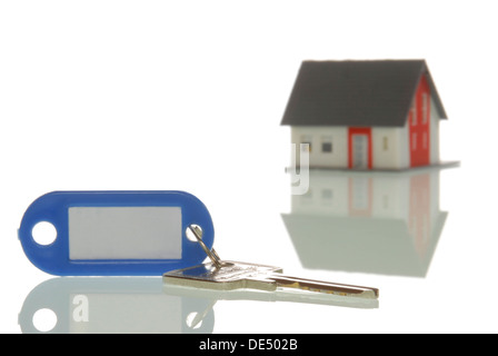 Key lying in front of a miniature house, symbolic image for property market - Stock Photo