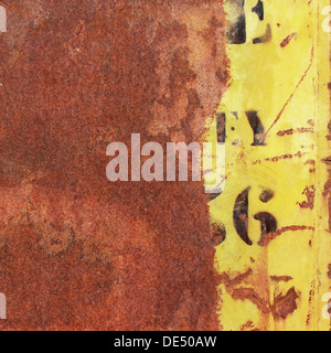 An Old Rusty Metal Background with Yellow Paint and Numbers, Letters - Stock Photo