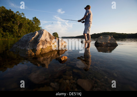 A man casts his line while fishing on Lake Windsor in Bella Vista, Arkansas. - Stock Photo