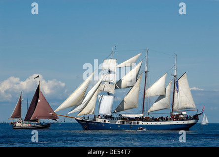 Meeting of a sail boat with a tall ship, three-masted barquentine, under full sail, Kieler Woche 2010, Schleswig - Stock Photo