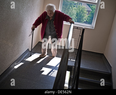 Independent elderly senior pensioner lady at 99 years climbing two flights of stairs aided only by her walking stick - Stock Photo