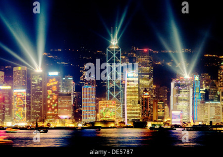 Hong Kong Island China city skyline of Central District at night with laser light show seen across Victoria Harbour - Stock Photo