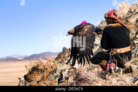A Kazakh eagle hunter releases his eagle for a hunt. - Stock Photo