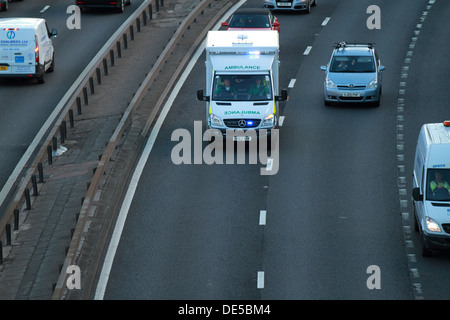 A Scottish Ambulance Service vehicle rushes down the M8 motorway with sirens and blue lights to an accident.