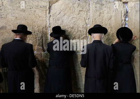 Jewish men praying at the Western Wall or wailing wall in Old city East Jerusalem Israel - Stock Photo