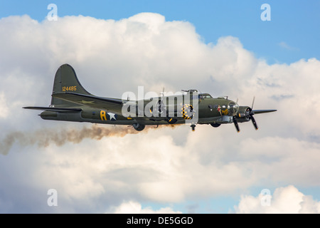 A Boeing B17 flying fortress WWII bomber in flight, with smoke coming from farside engine. - Stock Photo