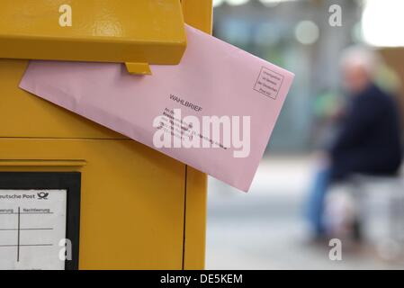 ILLUSTRATION - A person puts a postal voting letter for the 18th German federal election into a mailbox of the German - Stock Photo