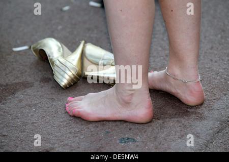 Paris, France, Detail, woman has taken off her high heel shoes - Stock Photo