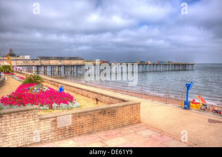 Teignmouth seafront promenade and pier Devon England, traditional English structure by the sea in HDR with red flowers - Stock Photo